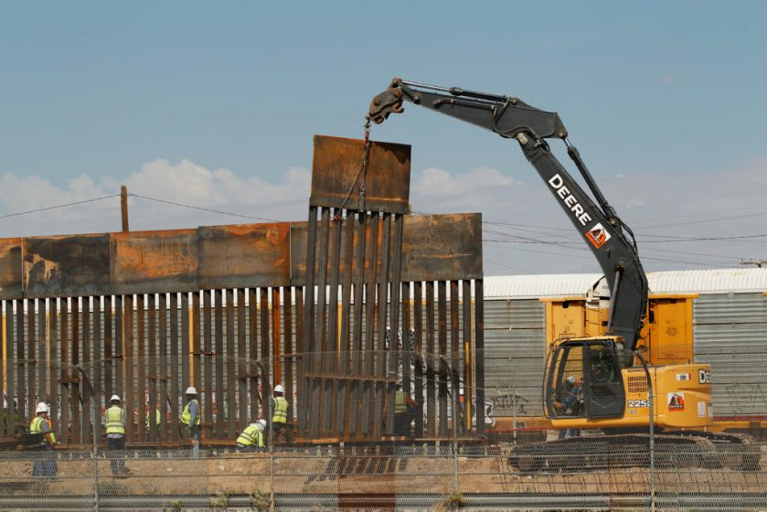 U.S. workers are seen next to heavy machinery while working on the replacement of a border fence in El Paso, as seen from the Mexican side of the border in Ciudad Juarez