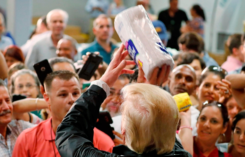 Image: President Trump throws rolls of paper towels to residents gathered in a chapel while visiting areas damaged by Hurricane Maria in San Juan, Puerto Rico